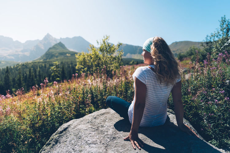 Young woman with curly long blond hair sitting on a rock looking at distant mountains Lost In The Landscape Beauty In Nature Casual Clothing Day Full Length Growth Leisure Activity Lifestyles Mountain Nature One Person Outdoors People Plant Real People Rear View Sitting Sunlight Tranquility Tree Women Young Adult Young Women