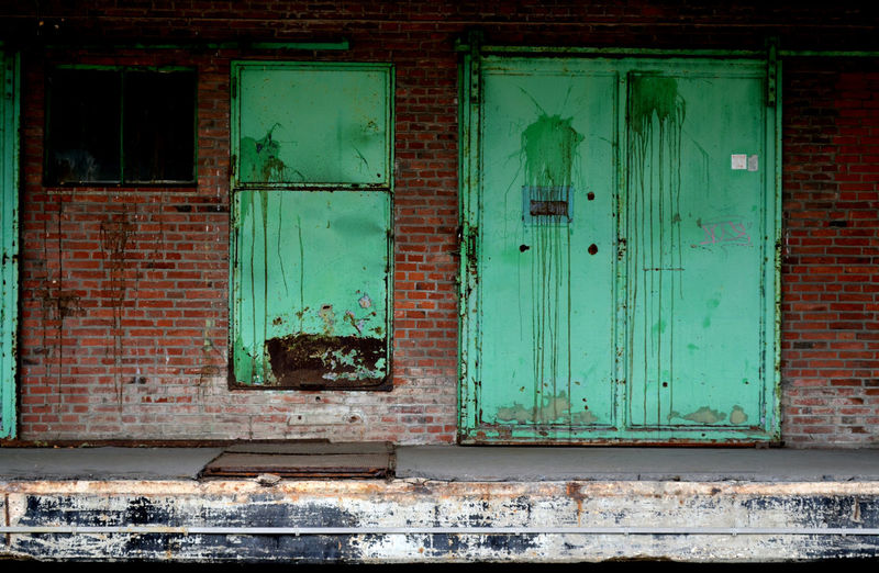 Abandoned Architecture Brick Building Building Exterior Built Structure City Closed Contrast Day Door Entrance Green Color House No People Old Outdoors Run-down Shabby Turquoise Colored Wall - Building Feature Warehouse Weathered Window