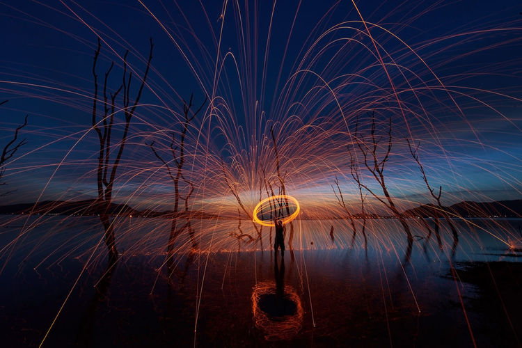 Man steel wool on fire in front of dead tree Beauty In Nature Blurred Motion Firework Firework Display Glowing Illuminated Light Long Exposure Low Angle View Motion Nature Night No People Orange Color Outdoors Reflection Sky Sparks Spinning Water Wire Wool
