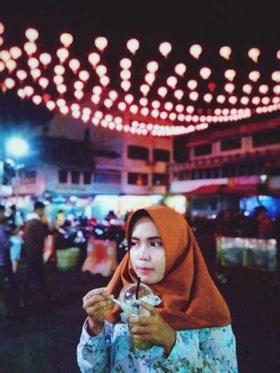 Portrait of woman holding ice cream at night