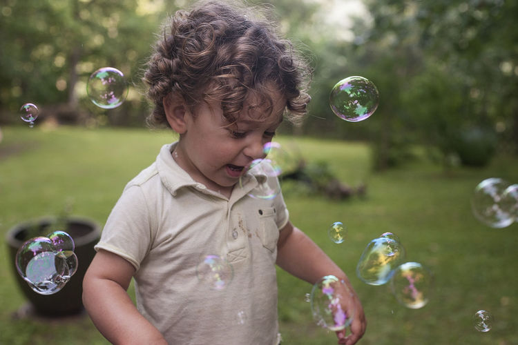 Boyhood Fun Blowing Bubble Bubble Wand Child Childhood Childhood Memories Day Focus On Foreground Fragility Front View Innocence Leisure Activity Males  Mid-air Nature One Person Outdoors Real People Soap Sud Transparent Vulnerability