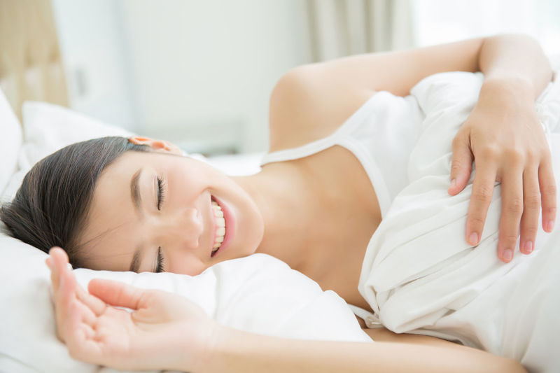 Adult Beautiful Woman Beauty Bed Eyes Closed  Furniture Indoors  Leisure Activity Lifestyles Lying Down One Person Portrait Real People Relaxation Smiling Women Young Adult Young Women