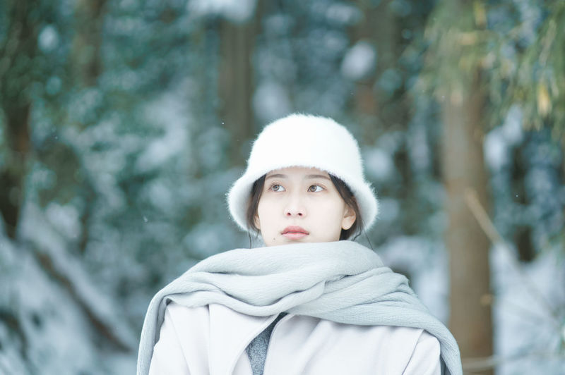Portrait of woman looking at tree during winter