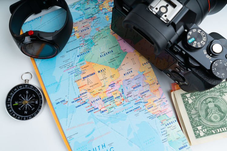 High angle view of map with camera and money on white background
