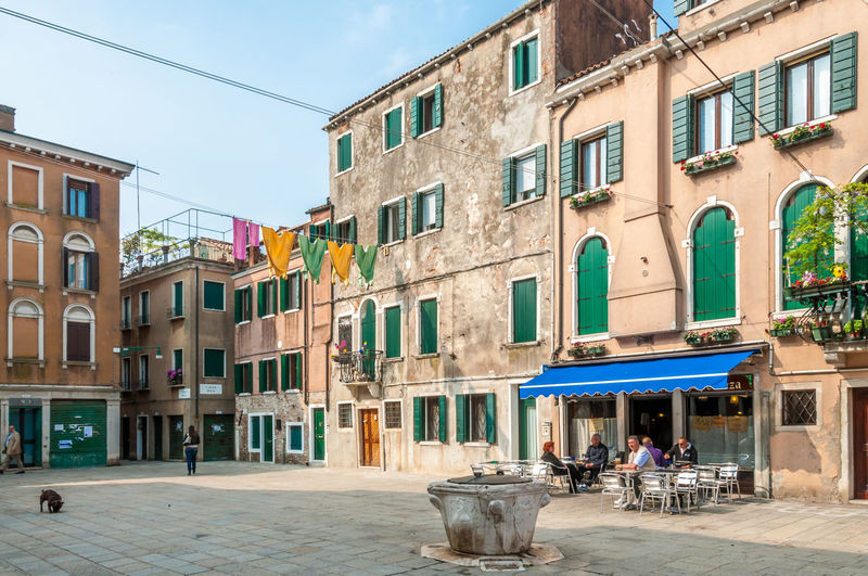 A typical residential area in Venice, Italy Italy 🇮🇹 Square Venice Italy Walking Peoples Architecture Bar Building Exterior Built Structure City Clothesline Dog Men Oldtown Outdoors People Pizza Restaurant Real People Residential District Restaurant Sidewalk Cafe Sitting In A Bar Washed Clothes Window Window Blind