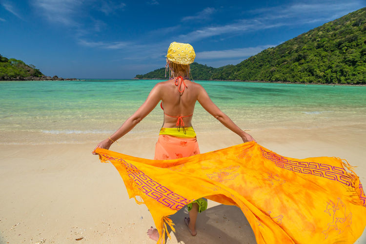 Back of happy and fashionable tourist woman with colorful sarong in turquoise water of Maya Bay famous lagoon of The Beach movie, Phi Phi Leh, Andaman Sea in Thailand Fashionable and happy tourist with sarong and pink wide-brimmed hat making a selfie on tropical famous beach of Nai Harn Beach, Rawai, Phuket, Thailand. Happy tourist enjoys panorama from Sail Rock View Point of kor 8 of Similan Islands National Park, Phang Nga, Thailand, one of the tourist attraction of the Andaman Sea. Happy woman with bikini and shorts, jumping in the air on Ya Nui Beach, a little cove divided by a rocky cape, Phuket, Thailand, Asia. Happy Koh Rok Islands Nui Beach Phang Nga Bay Phuket Thailand Tanning ☀ Thailand Vacations Woman Beach Beautiful Woman Beauty In Nature Day Girl Horizon Over Water Koh Rok Leisure Activity Lifestyles Longtail Boat Nature One Person Outdoors Phang Nga Rawai Real People Sand Scenics Sea Seascape Sky Standing Surin Islands Travel Destinations Tree Vacations Water Yellow Young Adult Young Women