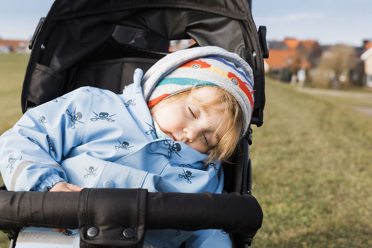 Close-Up Of Girl Sleeping In Baby Stroller On Field