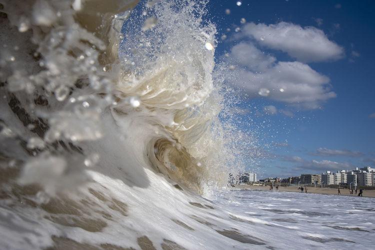 Sea waves splashing against blue sky