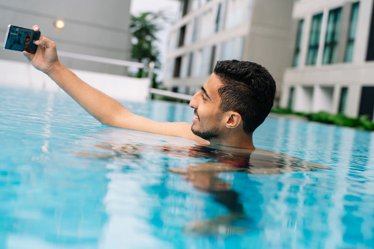 Portrait of man photographing in swimming pool