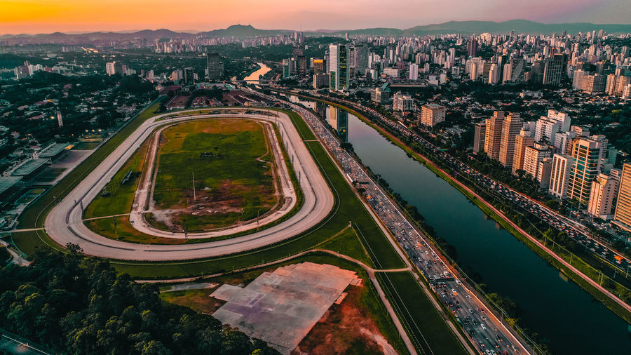 Aerial view of sports field in city against sky during sunset