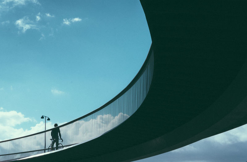 Low angle view of man on bridge against sky