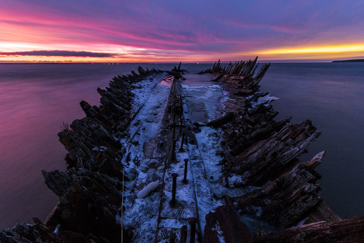 Shipwreck on sea against sky in winter during sunset