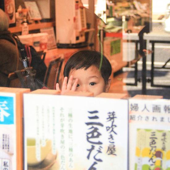 While I was walking around Ginza street, suddenly, a kid pops up from behind the window glass, waved and smiled at me warmly. Japan Warm Child Portrait Childhood Headshot Technology Close-up Elementary School Posing Human Connection