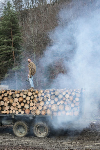 Young man standing on stack of wooden logs on truck