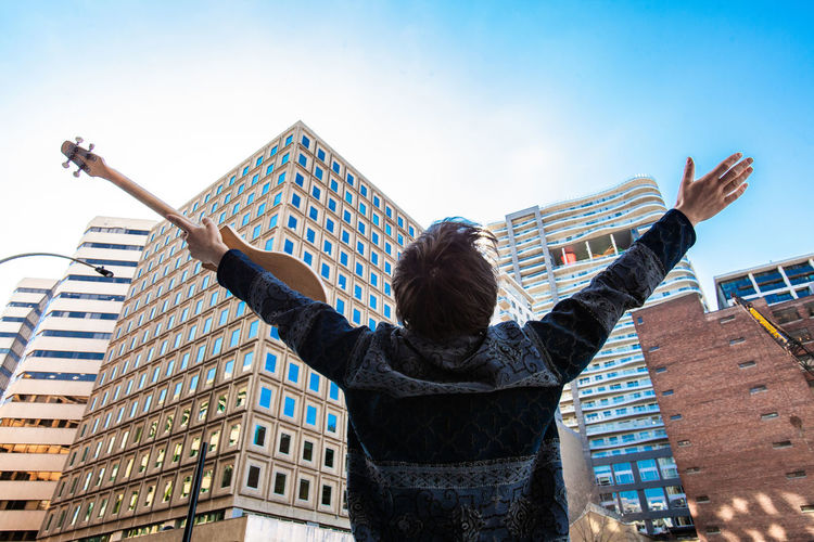 Rear view of woman standing by building against sky