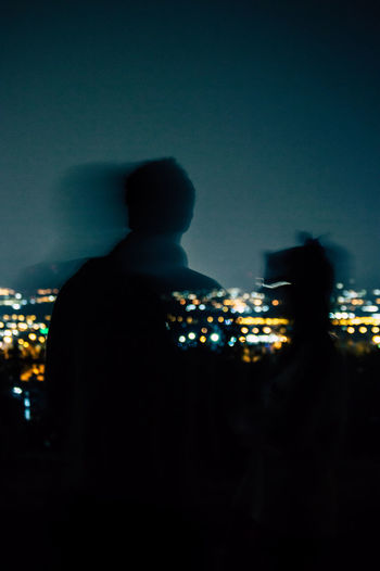 Rear view of silhouette man standing at illuminated city against sky at night