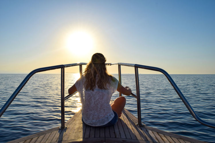 Woman on o ship looking into the sunset on the ocean Adult Beauty In Nature Fashion Hair Hairstyle Horizon Horizon Over Water Leisure Activity Lifestyles Nature Ocean One Person Outdoors Real People Rear View Scenics - Nature Sea Sitting Sky Sun Sunlight Sunset Water Women Young Adult