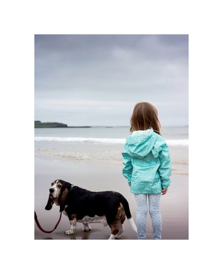 Rear view of woman with dog looking at sea against sky