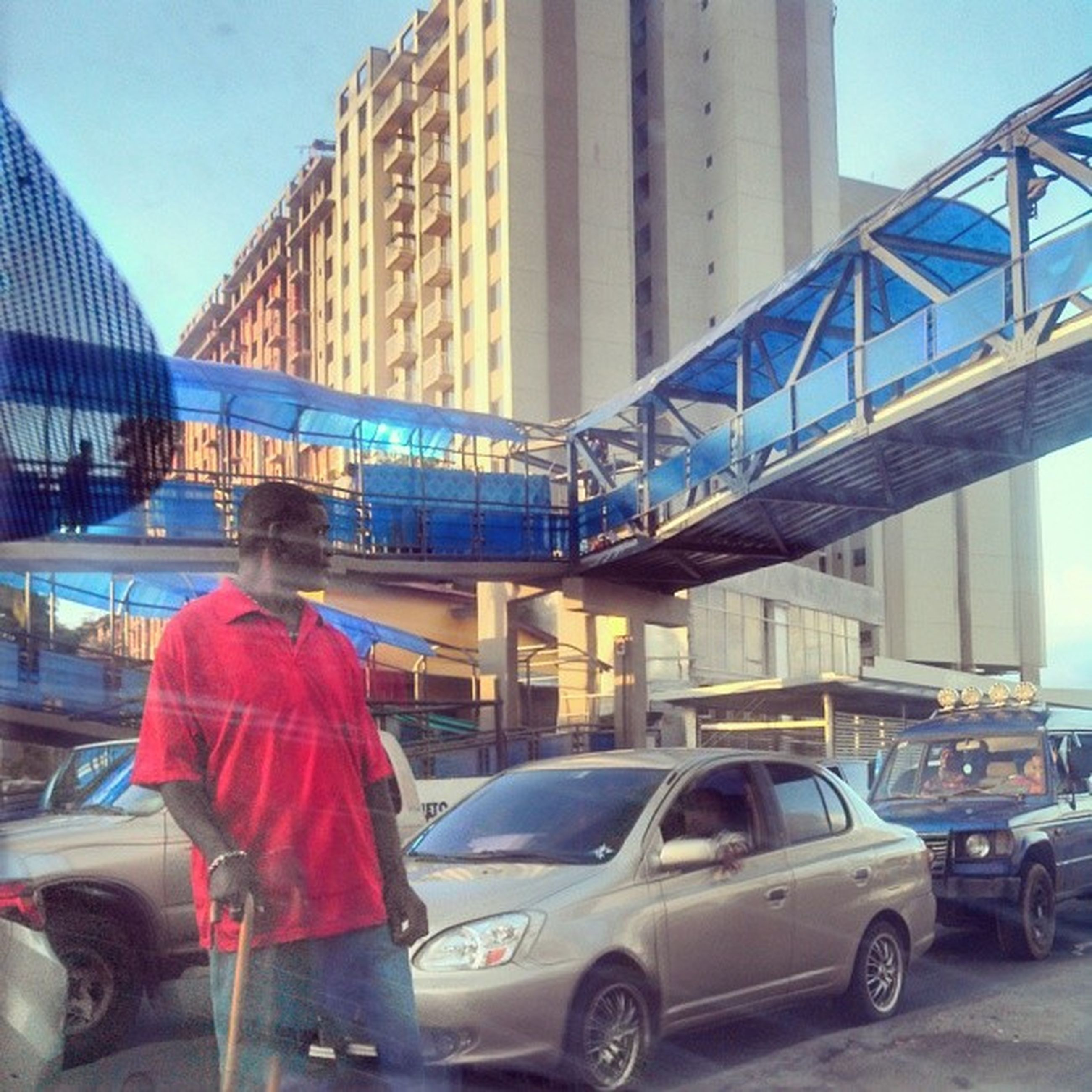 transportation, architecture, built structure, mode of transport, land vehicle, building exterior, car, city, travel, day, bridge - man made structure, street, sunlight, city life, incidental people, blue, outdoors, sky