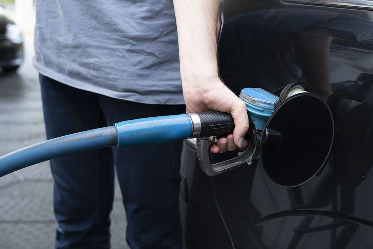 A male hand fills car with gasoline at the gas station holding a gaspump nozzle