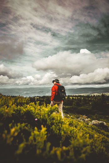 Rear view of man with backpack hiking on mountain against cloudy sky