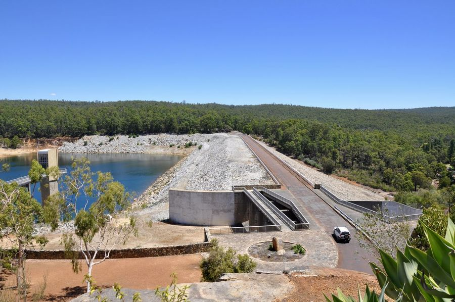 Elevated view over the Serpentine Dam and reservoir water with lush forest under a clear sky in Serpentine, Western Australia. Blue Breakwater Bridge Clear Sky Dam Day Elevated Elevated View Elevated Walkway Forest Outdoors Reservoir Reservoirs River Rock Scenics Serpentine Dam Spillway Tower Tranquil Scene Tranquility Uptake Wall Water WestCoast
