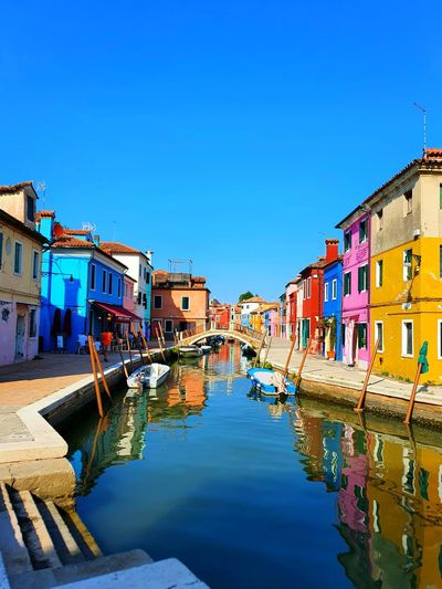 Canal amidst houses against clear blue sky