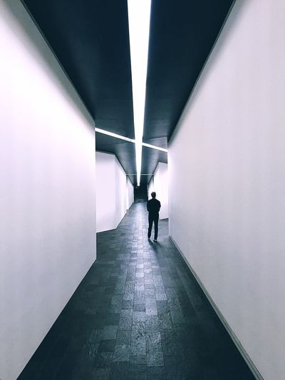 Man Walking In Long Corridor Along Walls