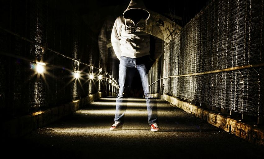 Hooded person standing in tunnel at night