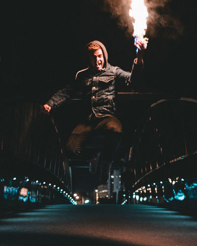 Portrait Of Man Holding Fire While Jumping Over Road At Night