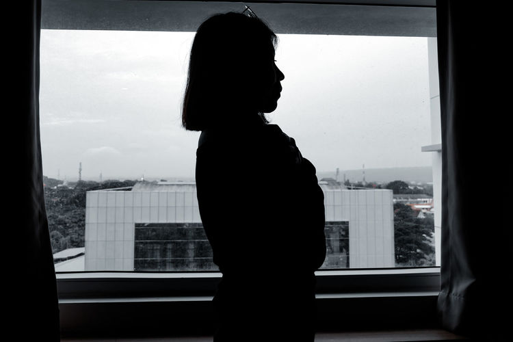 Silhouette woman looking through window in city
