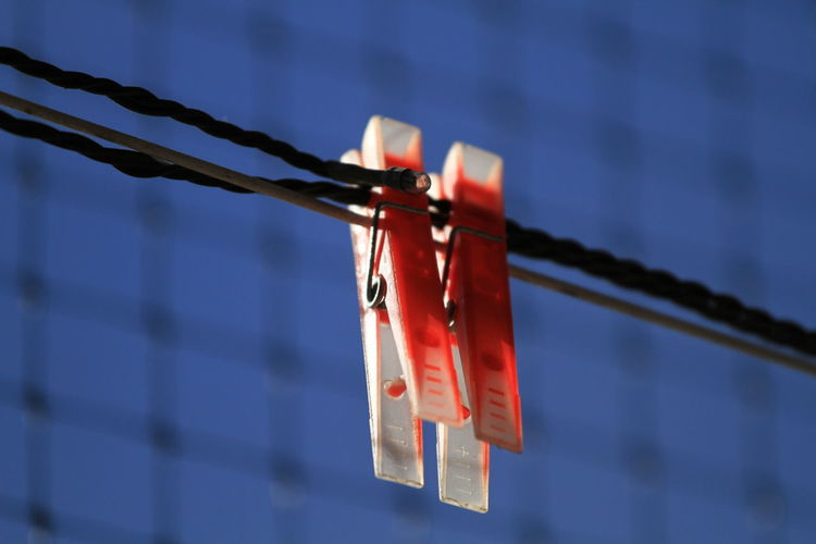 Close-Up Of Red Clothespins Hanging By Fence Against Sky