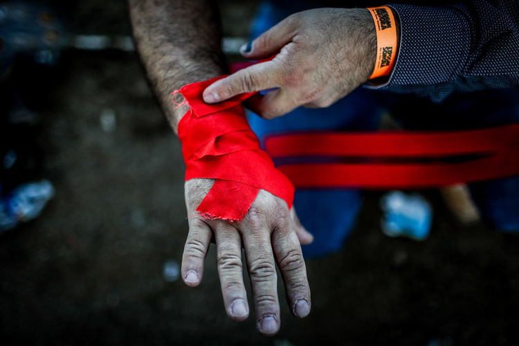 Midsection of man wrapping red bandage on hand