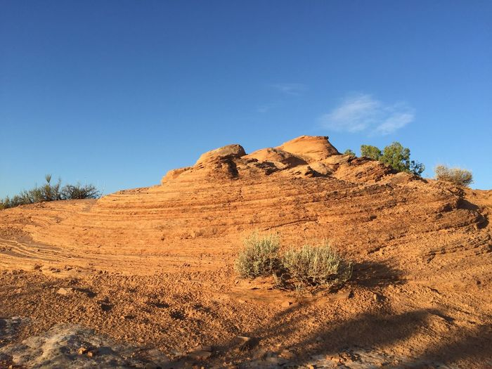 Rock formations in desert against blue sky