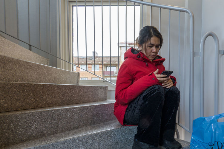 Woman using mobile phone while sitting on staircase