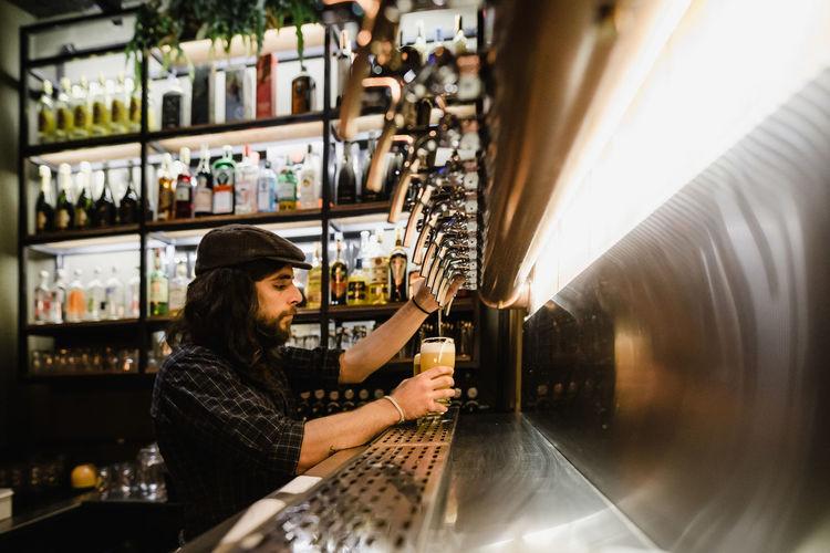 Side view of bartender filling beer glass at bar