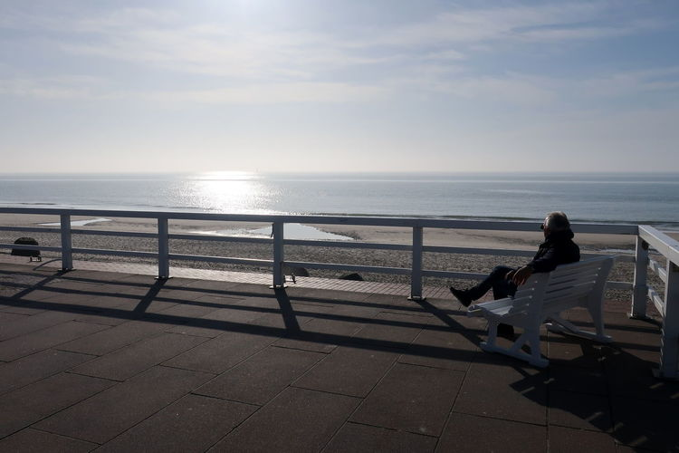 Man Sitting On Bench By Sea Against Sky During Sunny Day