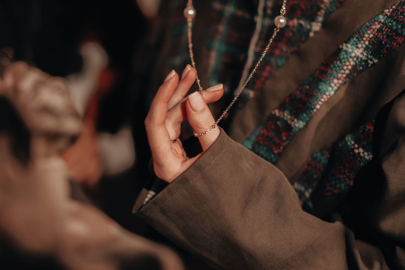 Female hand holding a gold chain