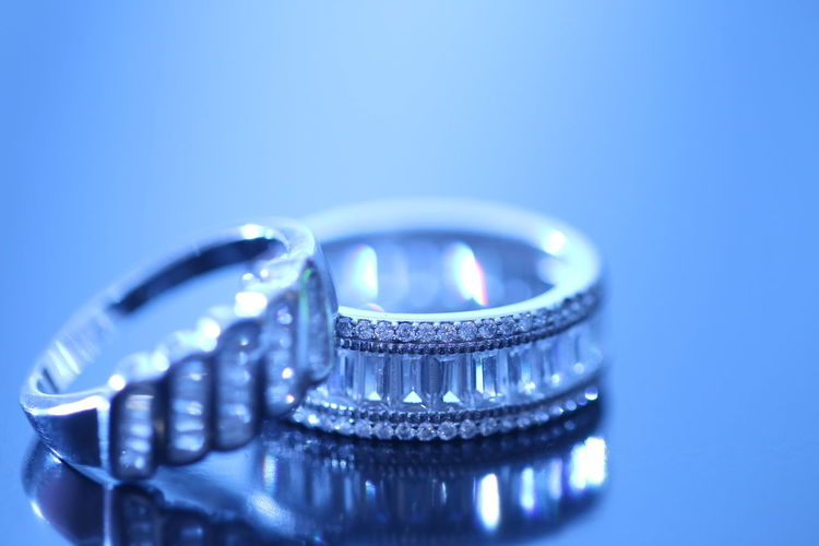 Close-up of wedding rings on blue background