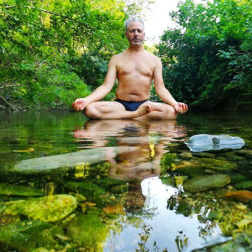 Full length of shirtless man in lake against trees