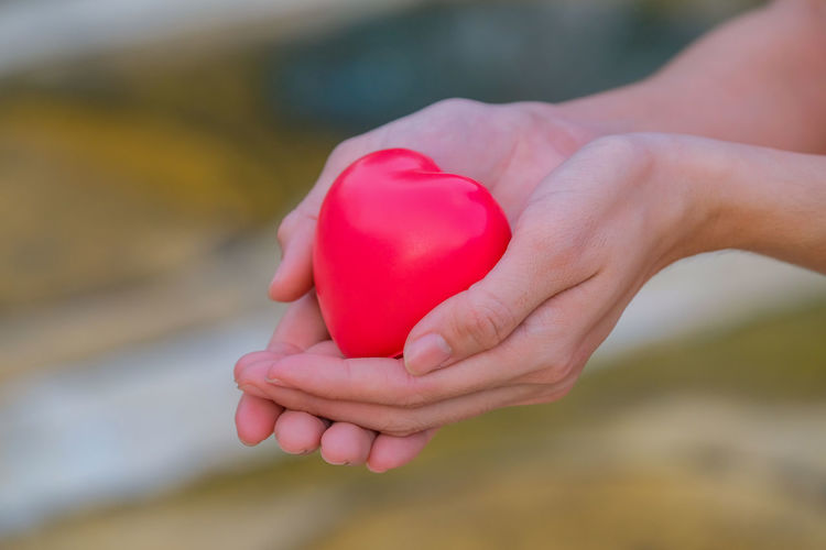 Close-up of hand holding heart shaped balloons