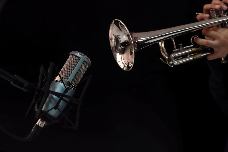 Microphone on Trumpet background Music Musical Instrument Arts Culture And Entertainment Black Background Brass Studio Shot Brass Instrument  Trumpet Indoors  Metal Artist Performance Musician Holding One Person Wind Instrument Playing Skill  Jazz Music Musical Equipment Silver Colored