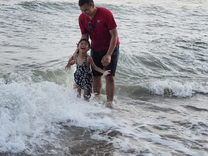 Man and son standing on shore at beach