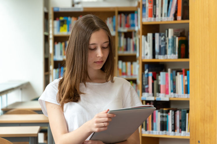 Smiling teenage girl holding file while standing in library