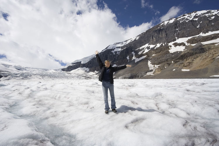 Woman With Arms Outstretched Standing On Snow At Jasper National Park