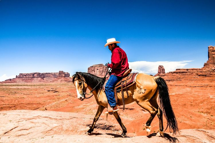 Monument Valley,Utah USA USA Animal Animal Themes Animal Wildlife Arid Climate Climate Cowboy Cowboy Hat Domestic Hat Horse Land Livestock Mammal Nature One Person Outdoors Pets Real People Ride Riding Sky Sunlight Vertebrate The Traveler - 2018 EyeEm Awards The Portraitist - 2018 EyeEm Awards
