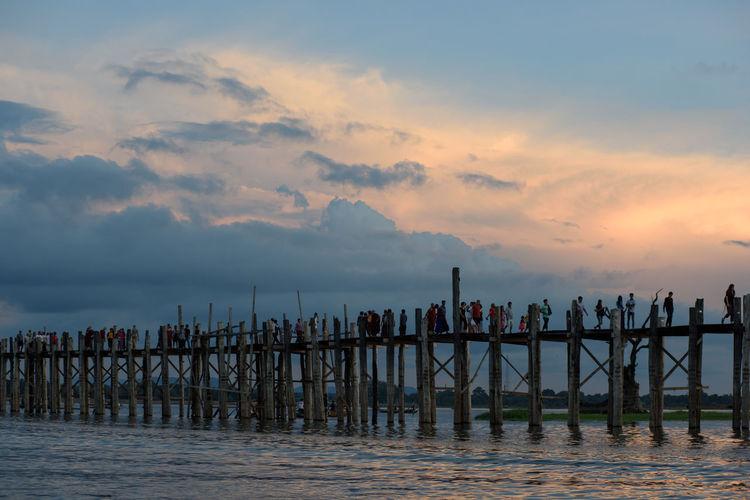 People on footbridge over sea against sky during sunset