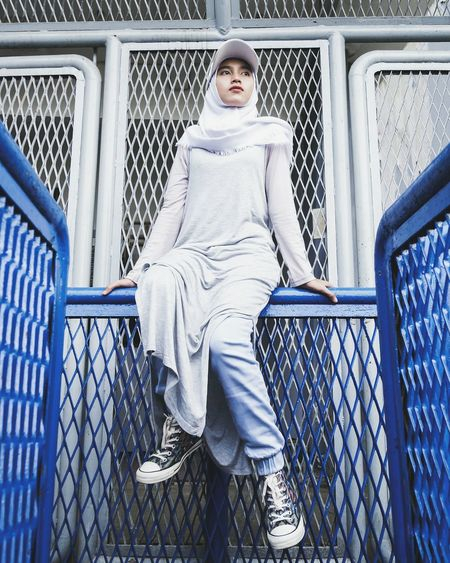 Low angle view of woman wearing hijab sitting on railing