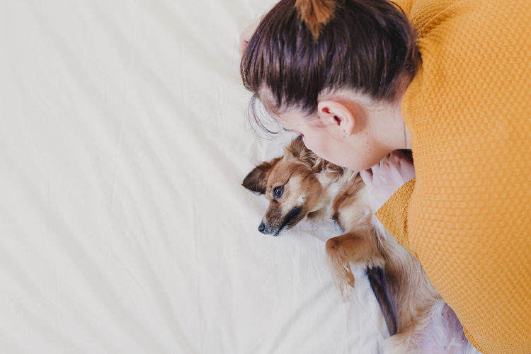 High angle view of woman with dog playing on bed at home