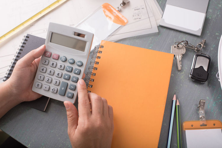 Cropped hands of woman using calculator at desk